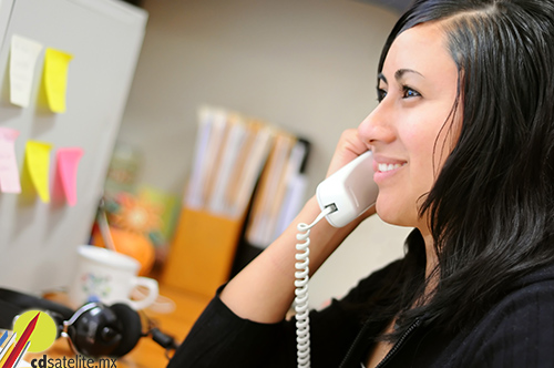 Young woman at the office, talking on the phone